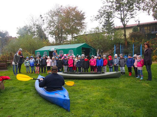 pogadanka dla dzieci o bezpieczeństwie na wodzie i kajakach. Instruktor prezentuje kajak. Dzieci przyglądają się.