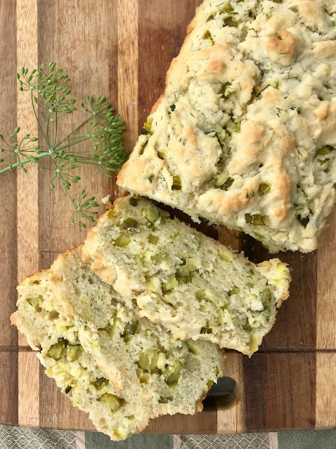 A loaf of dill pickle quick bread on a cutting board with slices.