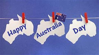 """Three Australia-shaped white cutouts hanging on a line with a small Australian flag. They spell out """"Happy Australia Day"""""""