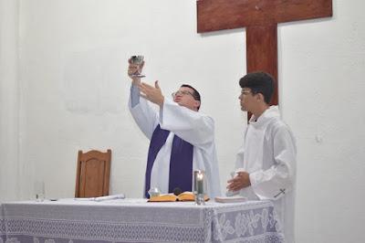 Padre erguendo o cálice na Santa Missa.