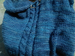 a large piece of stocking stitch in dark blue yarn.  Two 4 stitch cables are centered in the knitting.