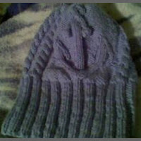 A blue beanie style hat featuring cabled anchors at the front and back, and basic cables on the sides