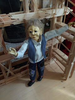Puppet standing on a small stage made by artist Dominic Fee