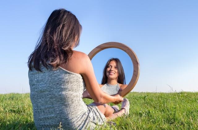 vajzë duke u parë në pasqyrë