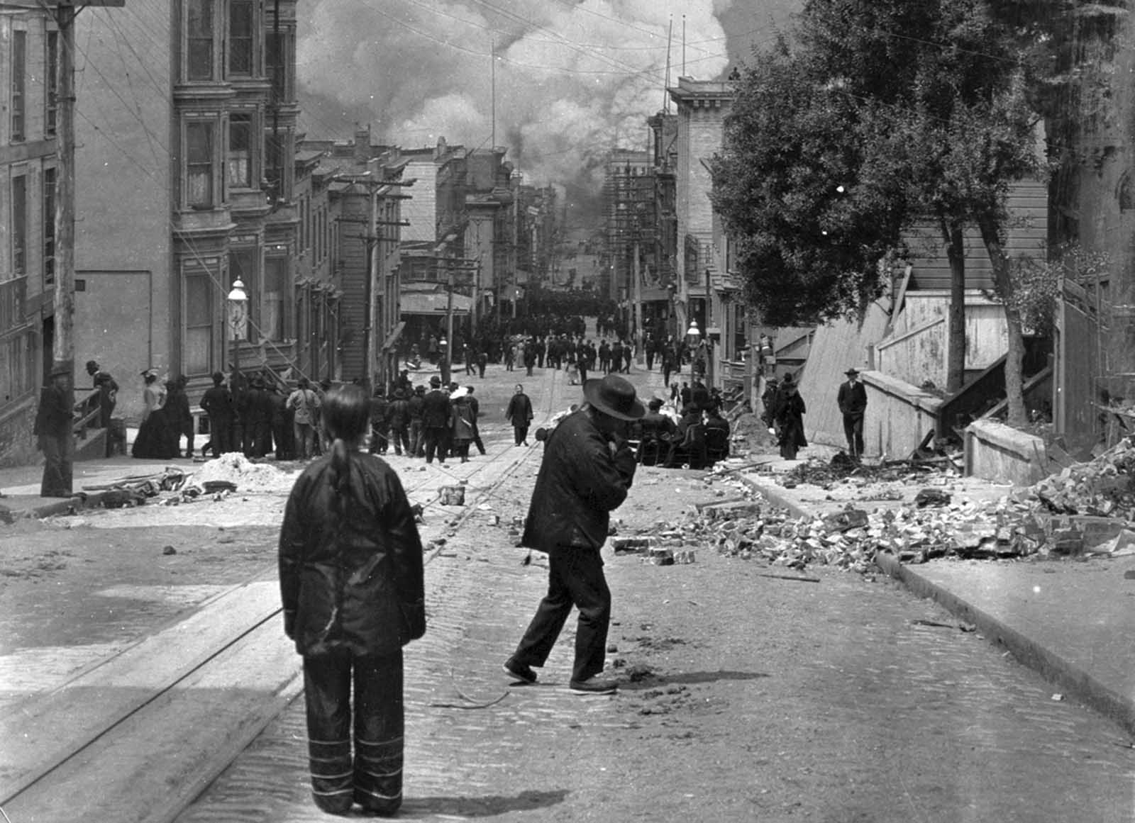 San Francisco residents stand in the rubble-strewn streets watching the fire grow after the earthquake struck on April 18, 1906.