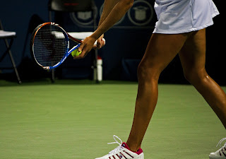 Image of female tennis player ready to serve