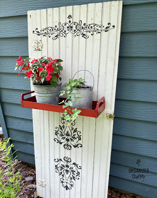 Photo of old cabinet door repurposed as a decorative junk garden plant holder