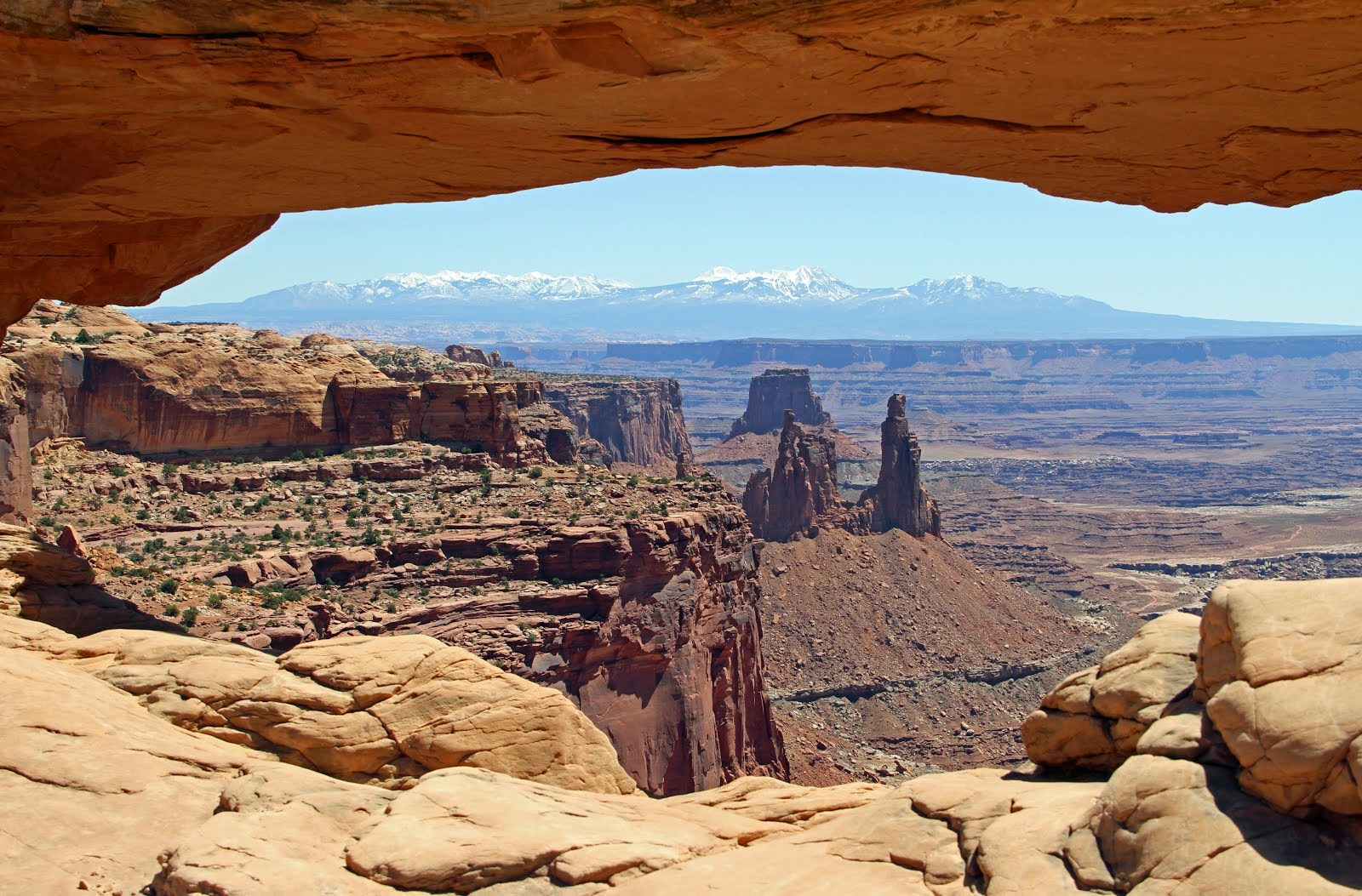 View of the La Sal Mountains through Mesa Arch carved into the Navajo Sandstone in Canyonlands