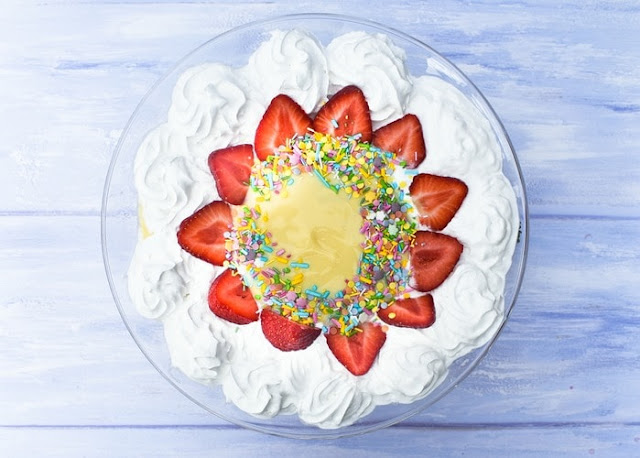 Overhead shot of strawberry trifle finished of with cream, strawberries and sprinkles