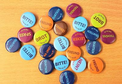 """Kolorowe przypinki z niemieckimi napisami, np. """"bitte"""", """"spass""""."""