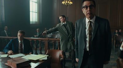 A man enters a courtroom to kill Jimmy Hoffa (Al Pacino) while Bill Bufalino (Ray Romano) has his back turned in a movie scene for The Irishman, a Netflix original directed by Martin Scorsese