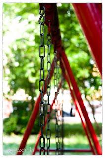 Játszótéri pirosra festett hinta a lakótelepen