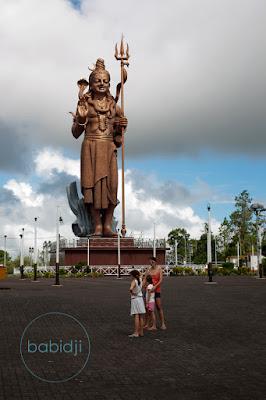 Babidji et ses filles devant la statue géante de Shiva au temple Ganga Talao à l'Île Maurice