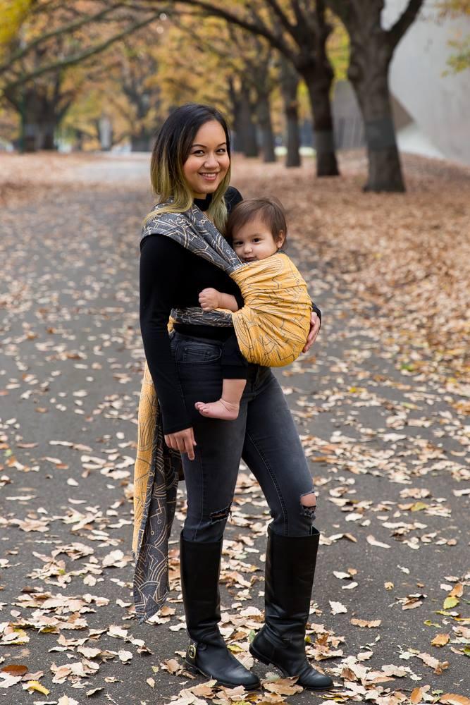 Woman wears baby in Wrapture Empire Metropolis wrap