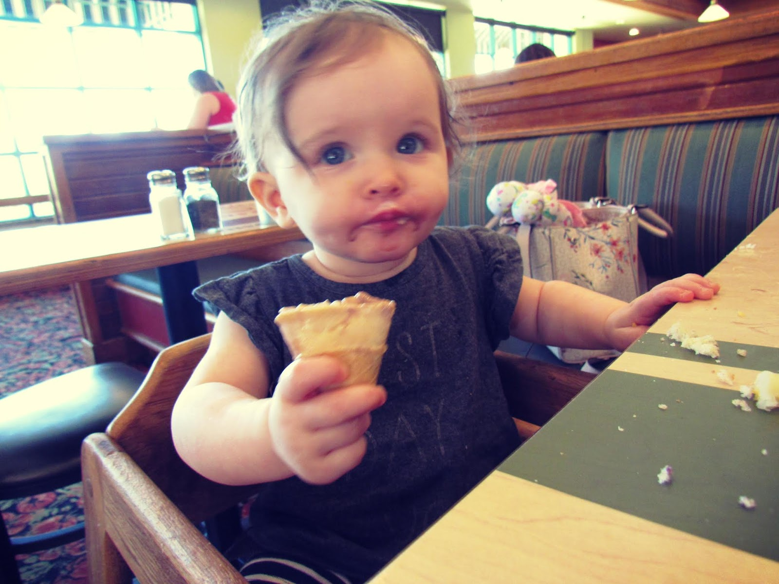 a baby girl eating a mini ice cream cone at a restaurant in Florida