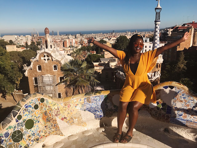 Abby sitting at viewpoint of Park Guell, Barcelona in orange Asos dress