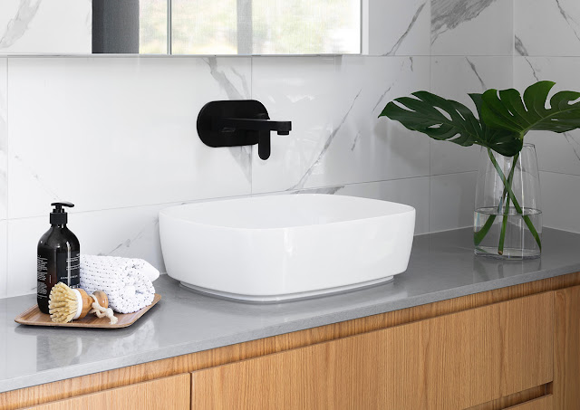 A mid-century modern bathroom vanity is softened with tropical foliage.