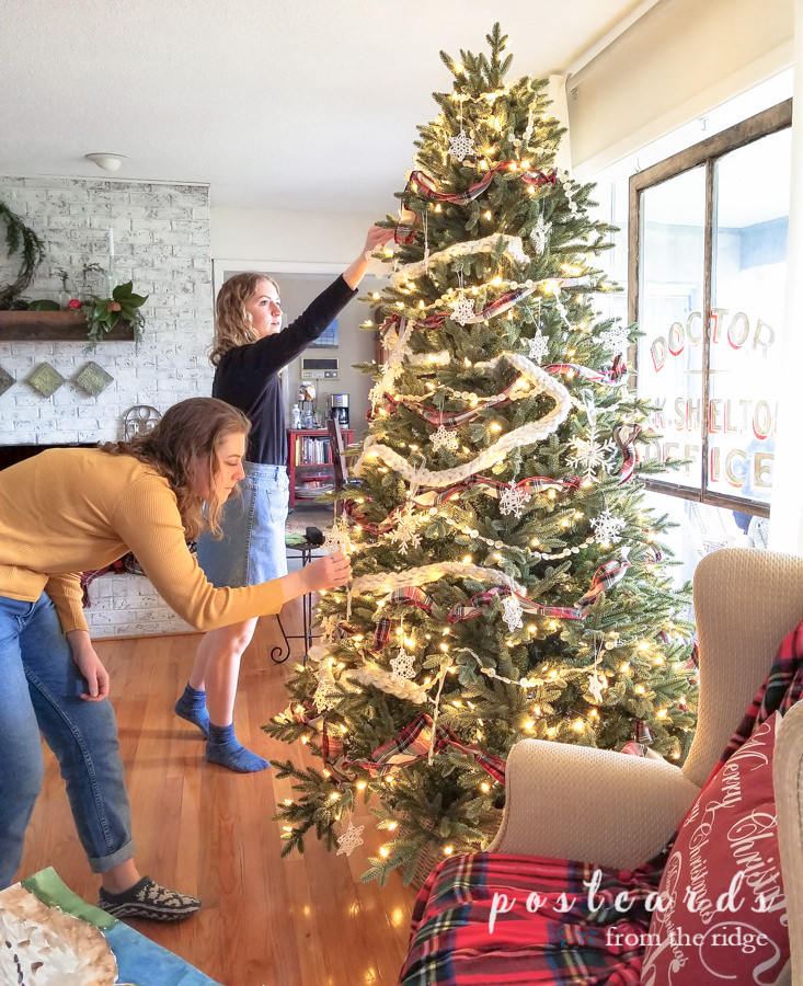 girls decorating an artificial Christmas tree