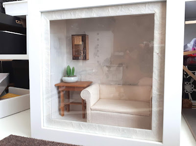 White box frame containing a 1/12 scale modern miniature cream sofa, with a wooden table next to it. On the table is a potted cactus, and above it is a book-themed piece of assemblage art.