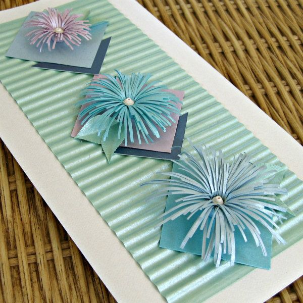 greeting card with vertical trio of large asymmetric fringed paper flowers with leaves
