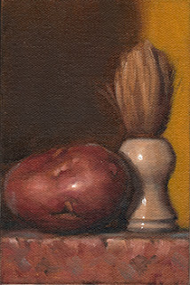 Still life oil painting of a Désirée potato beside a shaving brush.