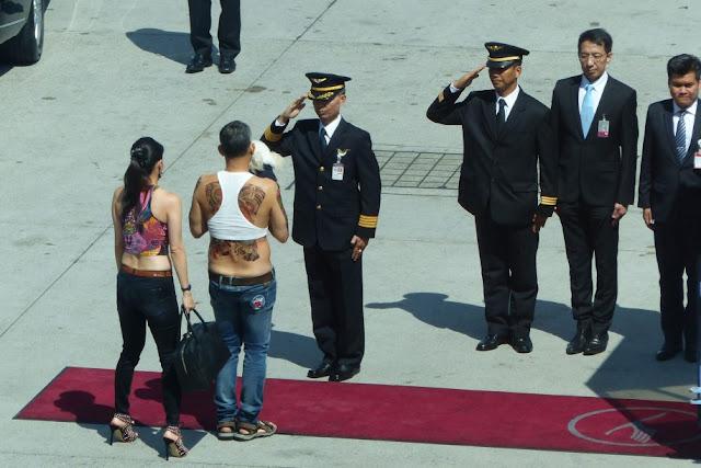 O príncipe herdeiro Maha Vajiralongkorn, 64, apareceu no aeroporto de Munique recentemente, com sua flacidez em um jeans, tatuagens falsas com um poodle e uma prostituta de luxo