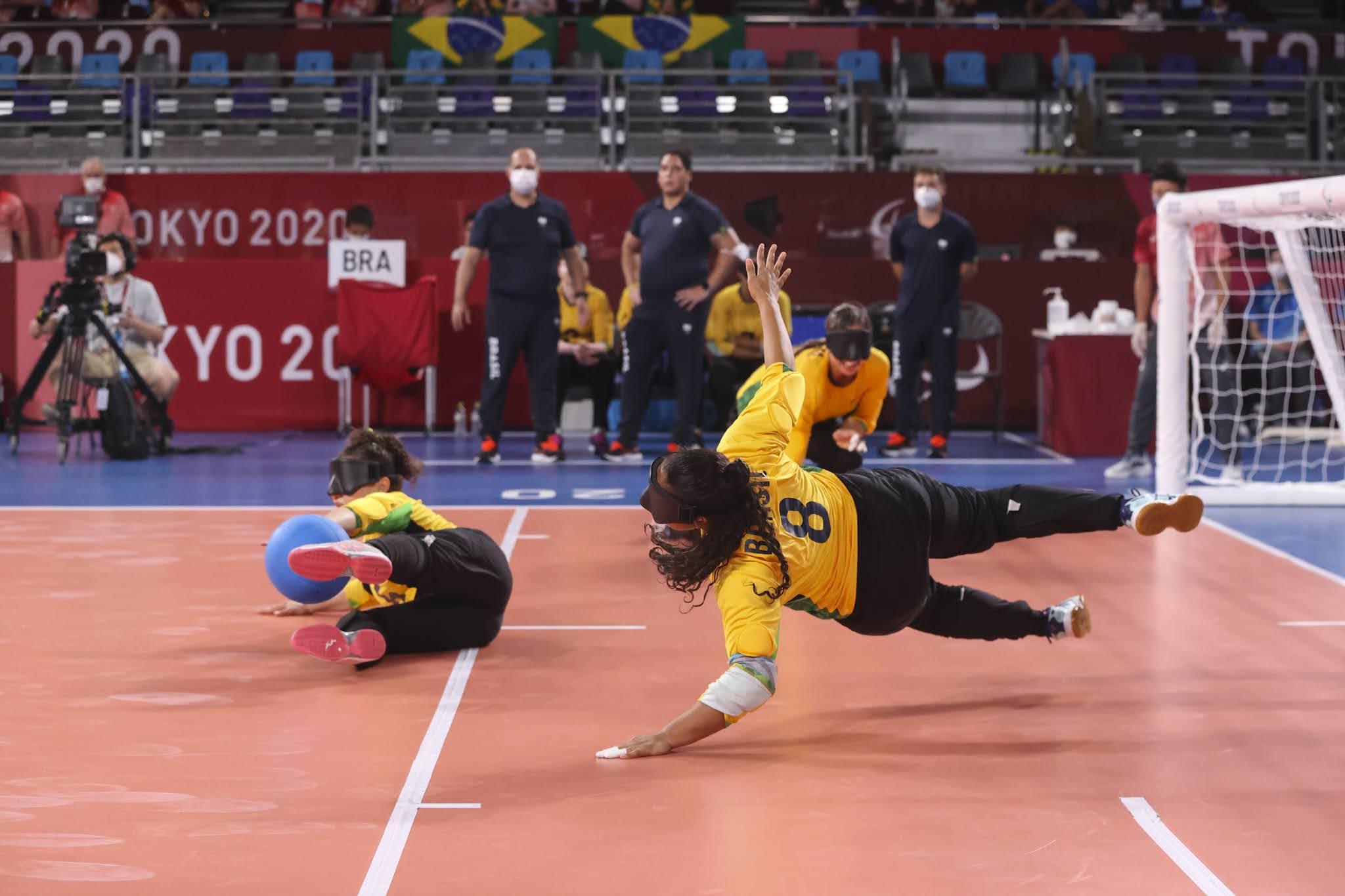 A jogadora Jéssica Gomes, de amarelo, salta deitada para tentar defender a bola em azul, que bate em sua companheira de equipe. O piso da quadra é laranja e a área técnica está ao fundo com piso azul