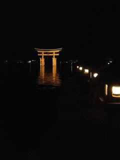il torii illuminato, c'è una fila di lanterne accese lungo tutto il lungomare