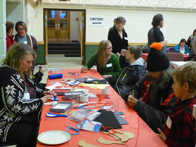 Group of party attendees focusing on making a holiday craft.