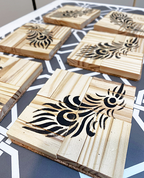 Black feathers on wooden coasters