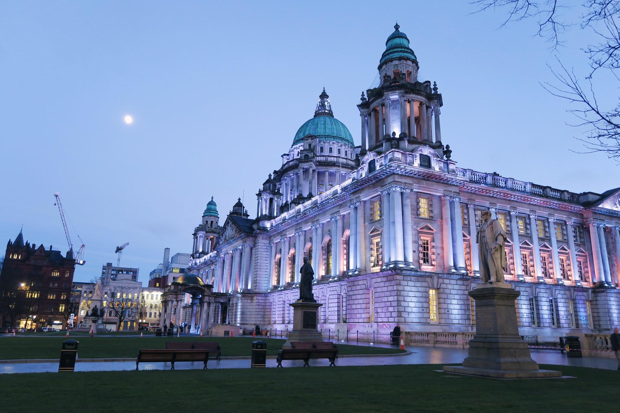 Belfast City Hall lit up by purple light at night