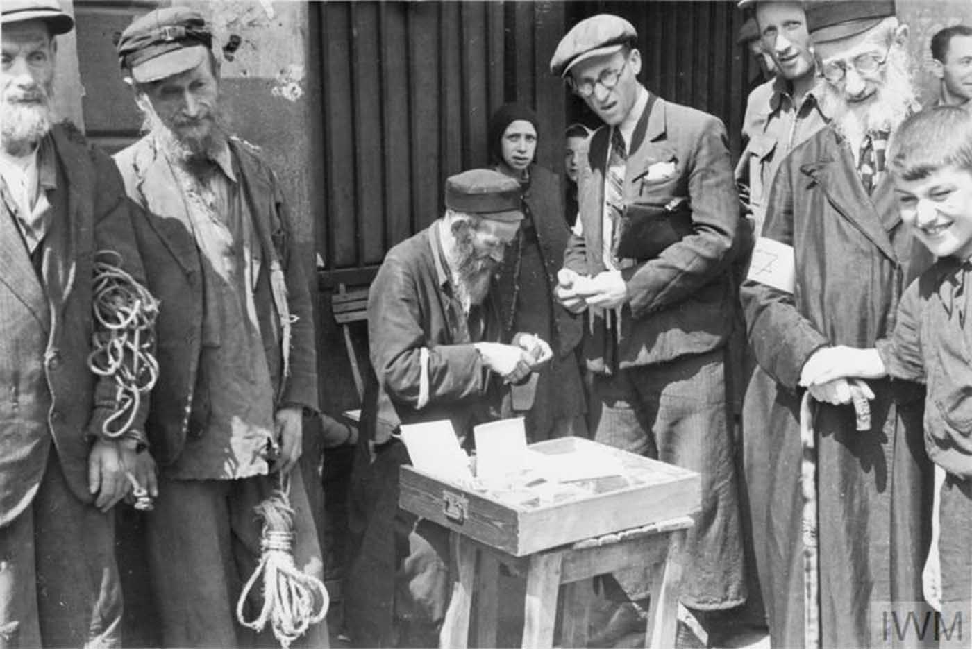 An armband seller making a transaction in the street of the ghetto. Note two elderly Jewish men on the left, probably selling pieces of rope.