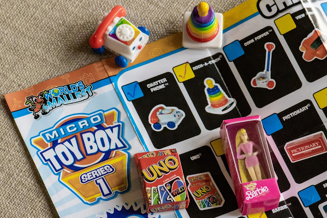 A corner of one side of the micro Toy Box Series 1 check list with 3 of the toys  on top of it next to ticked boxes