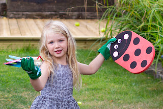 A 4 year old girl in a dress with green gardening gloves, gardening tools and a ladybird kneeling map