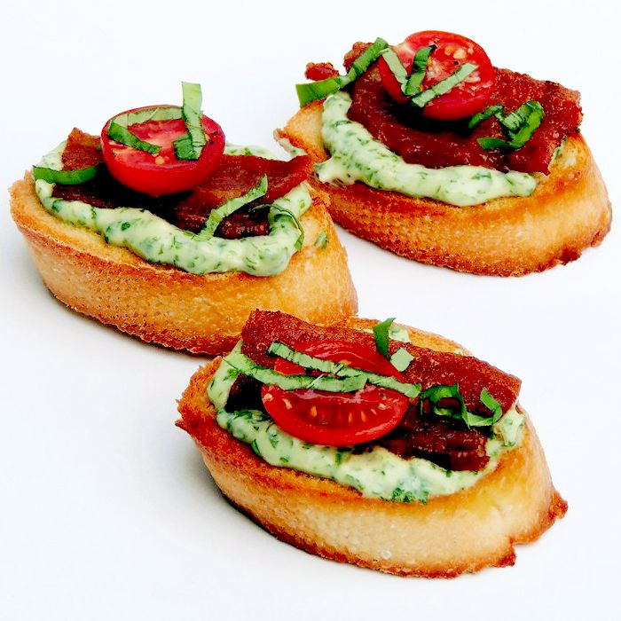 Crostini topped with basil mayonnaise, bacon, half of a grape tomato, and chopped basil, on a white background