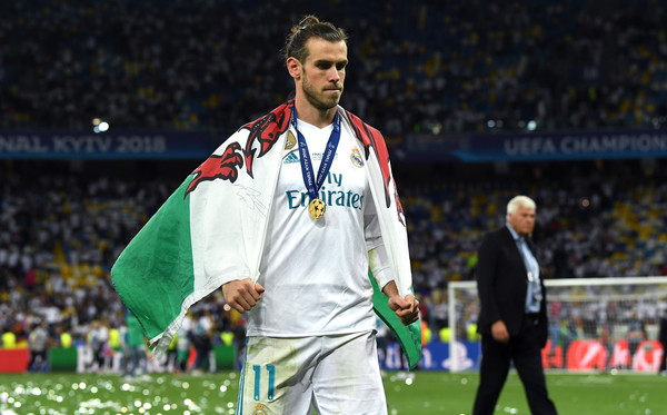 Gareth Bale of Real Madrid walks off the pitch with a Wales flag drapped over him after the UEFA Champions League Final between Real Madrid and Liverpool at NSC Olimpiyskiy Stadium on May 26, 2018 in Kiev, Ukraine