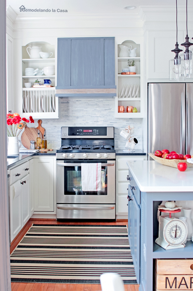 white and grey with red/orange pops of color - stripped rug and wooden elements.