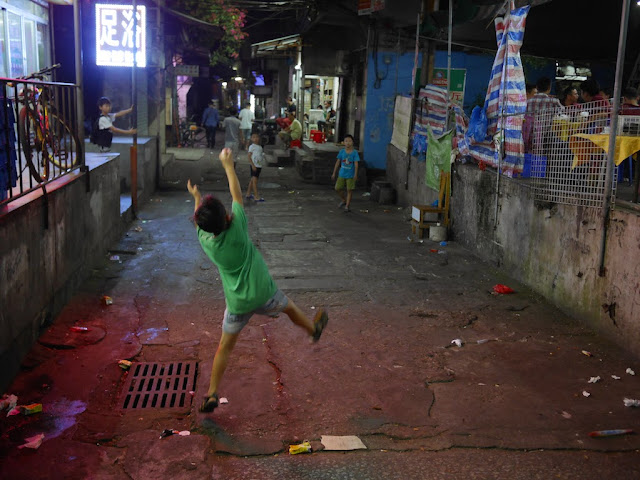 boy catches a paper ball at night in Zhuhai, China