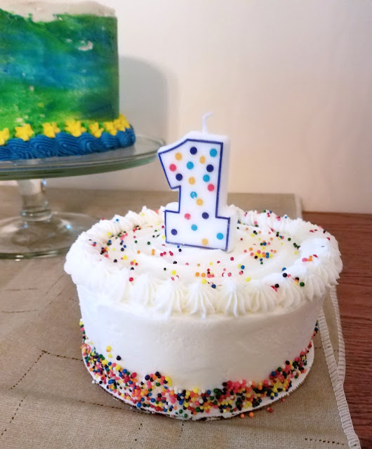small round layered cake with white icing and nonpareil sprinkle decorations