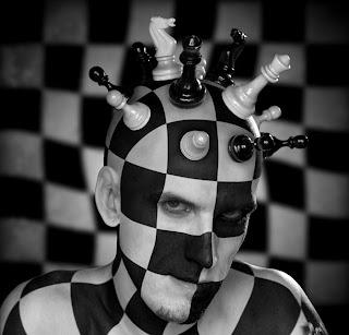 Hombre tablero de ajedrez con piezas en la cabeza