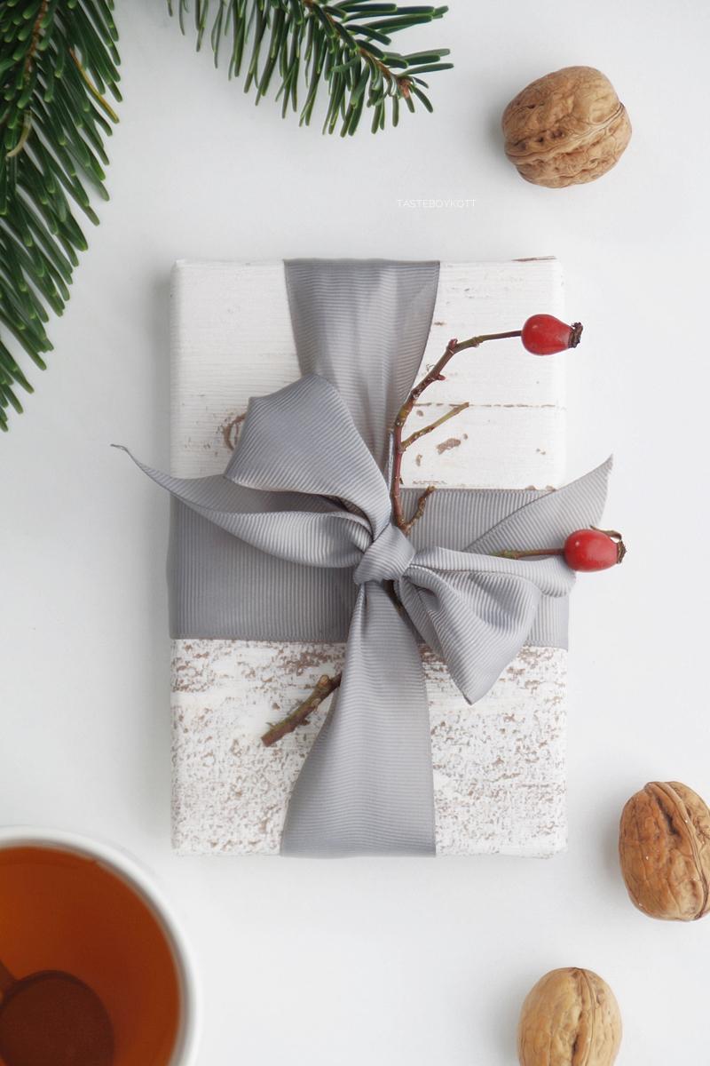 Weihnachtsgeschenke kreativ verpacken - DIY-Ideen. Tapetenmuster als Geschenkpapier, großes Band und Hagebuttenzweig als Deko. Tasteboykott Blog.