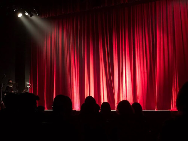 Image of a red closed theatre curtain and stage