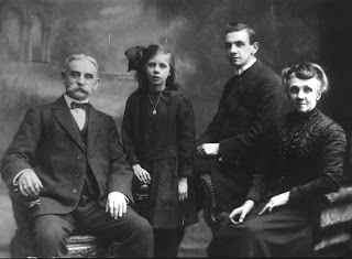 A greyscale photo of four people.  An elderly man with a very bushy mustache, a young girl with a big bow in her hair, a man in his twenties seated on the arm of a chair and in that chair an elderly woman, very smart.  All are wearing dark coloured clothes.
