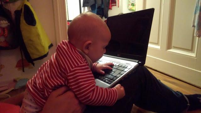 Babysohn schlägt auf eine Laptop-Tastatur ein