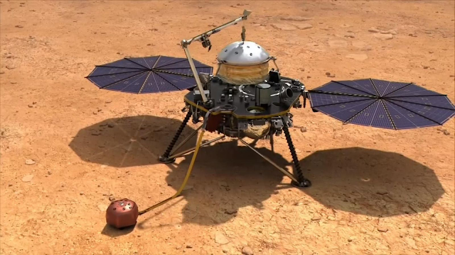 The seismometer is inside the white domed shield which is attached to InSight on the planet Mars.
