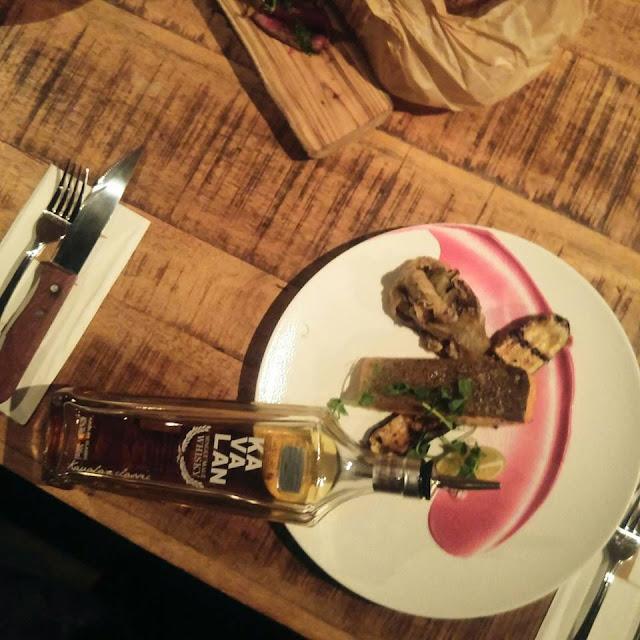 בתמונה: שולחן אוכל מעץ עליו מונחת צלחת עם מנת דגים ובקבוק ויסקי קוואלן. צילום: יחסי ציבור