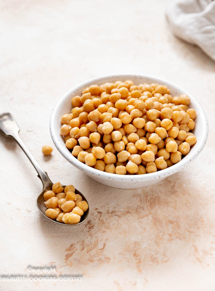 Instant pot cooked chickpeas in a beige bowl with a spoon