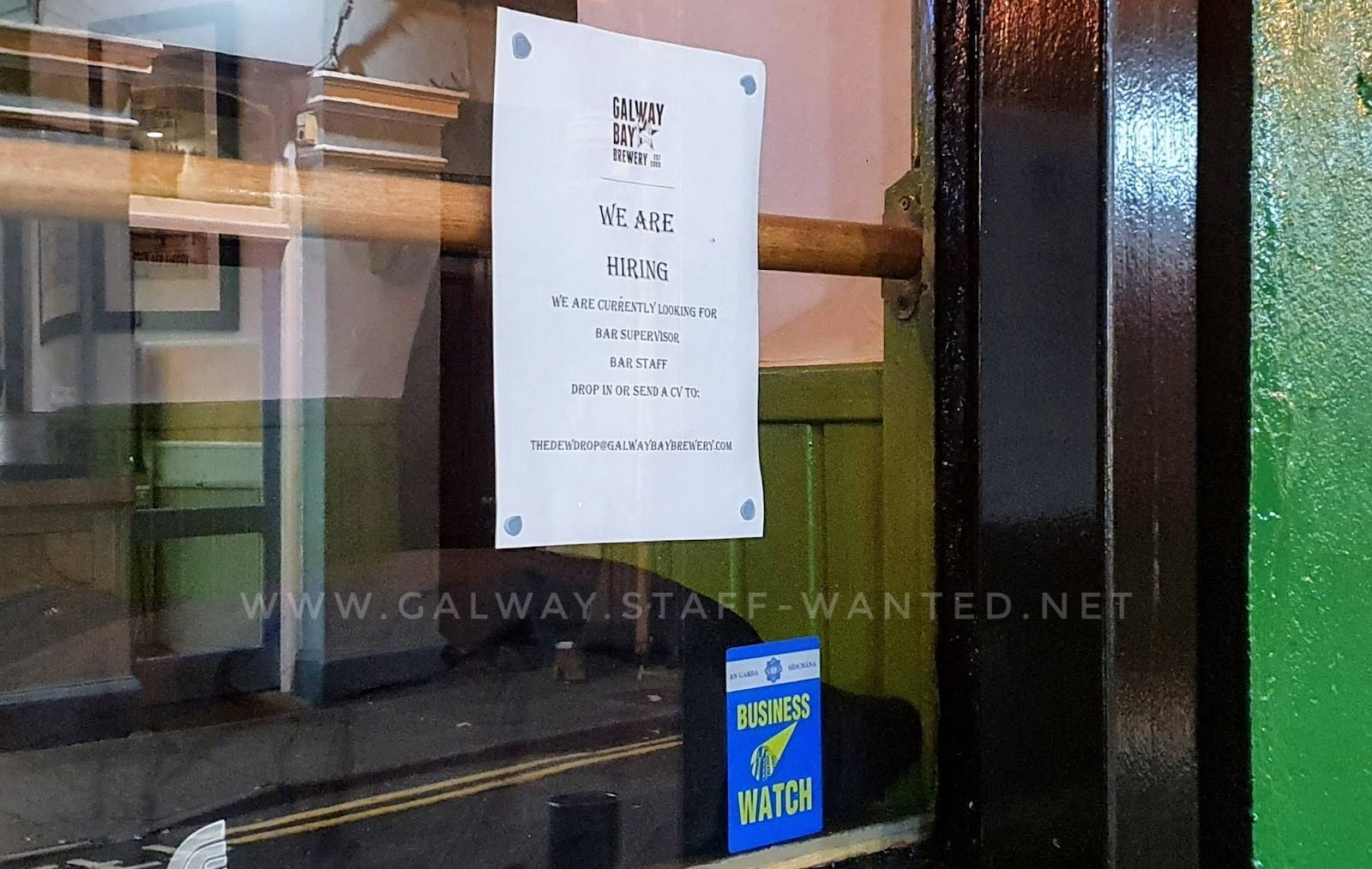 Galway bar window with a job advertisement and an Irish police Business watch sticker