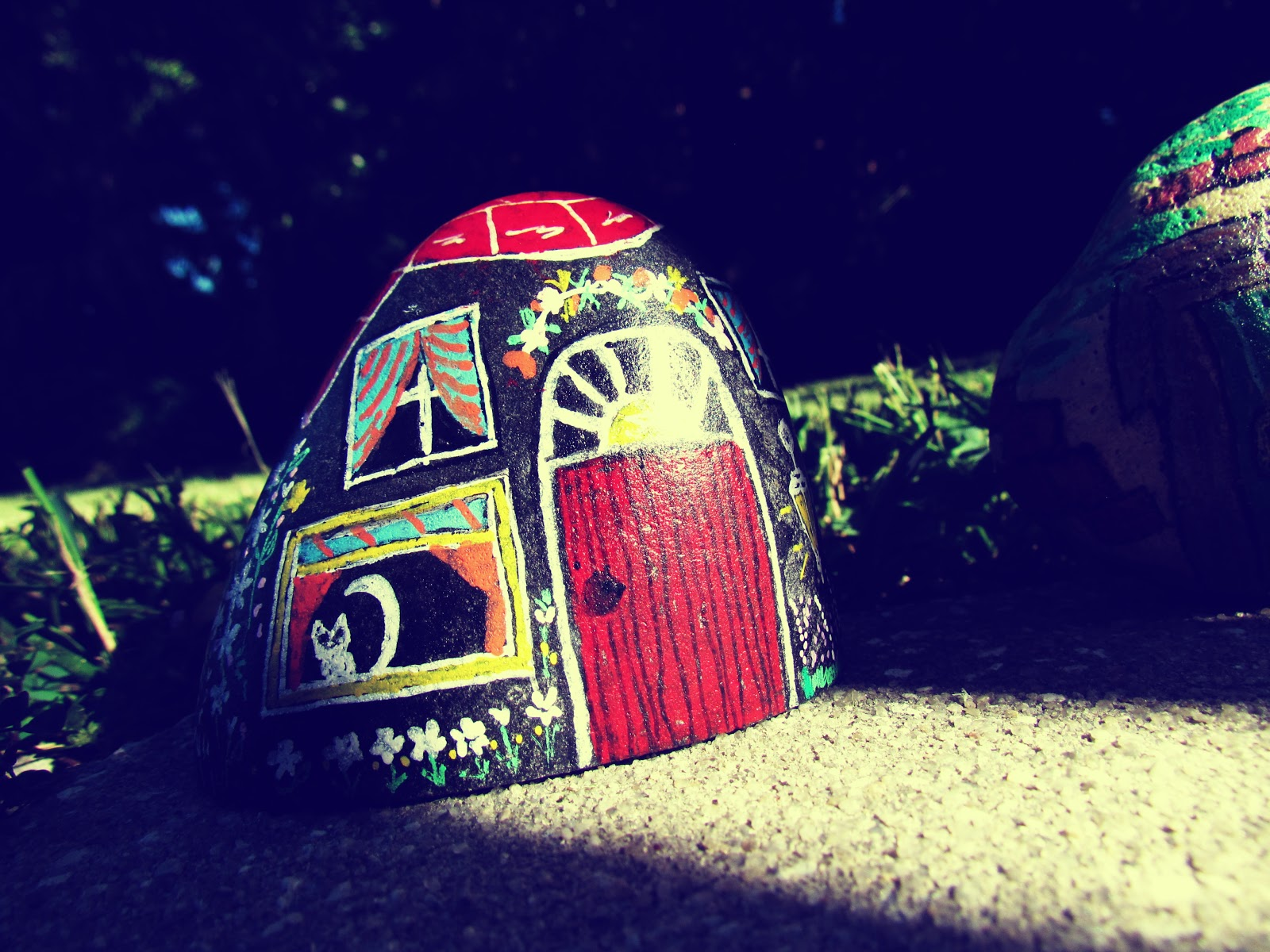 A painted rock fairy house on the grass in a backyard in mother nature