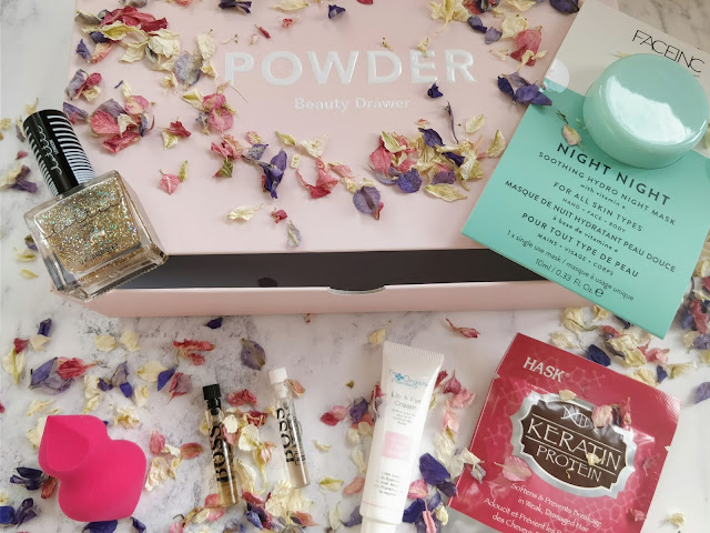 The contents of the November Powder Beauty Drawer arranged with dried petals around the pink drawer.